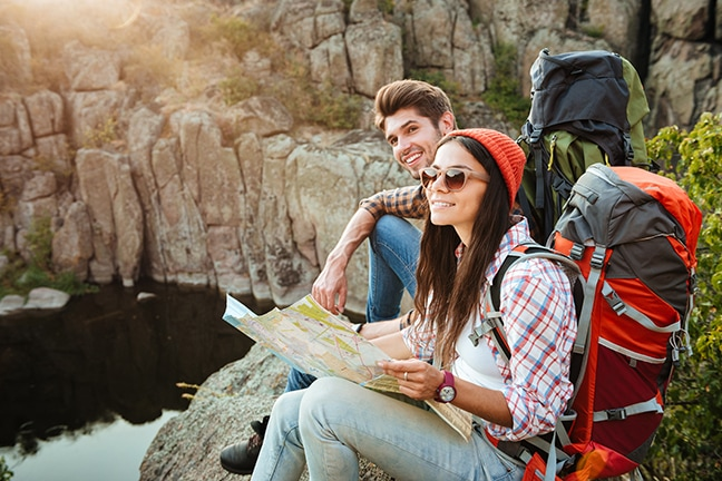 Intimate relationship couple hiking and looking at a map together